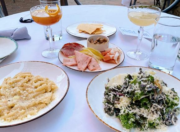 plates of pasta, salad, charcuterie, and cocktails on a white tablecloth on a patio