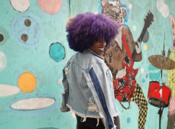 woman walking by a mural with flare-leg pants, a distressed light demin jacket, and purple afro hairstyle
